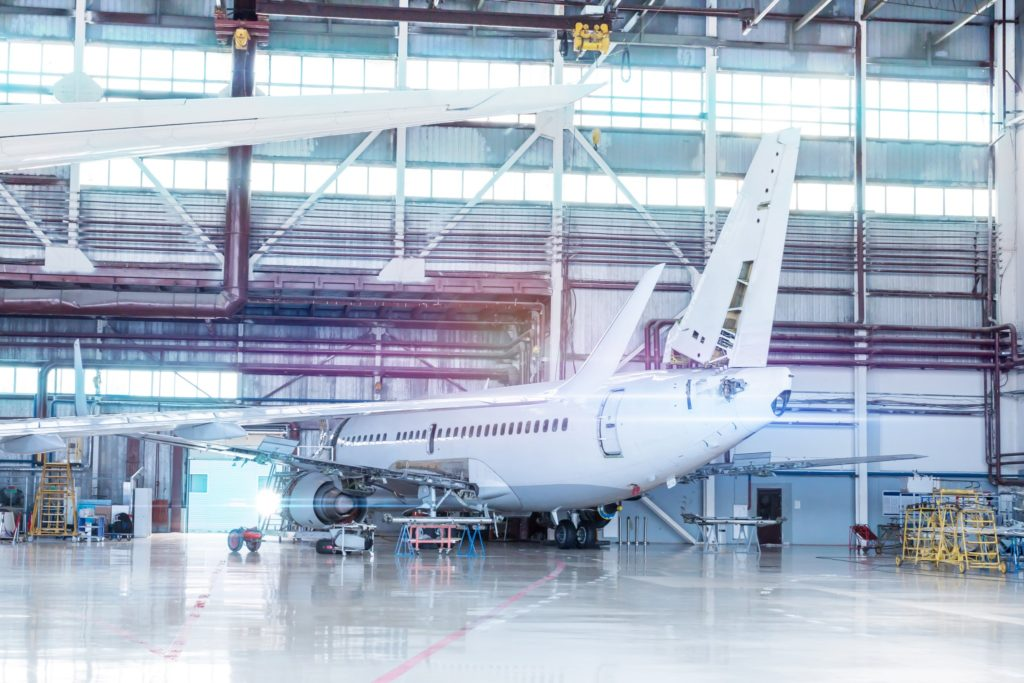 Passenger aircraft under maintenance. Checking mechanical systems for flight operations. White jet plane in the hangar