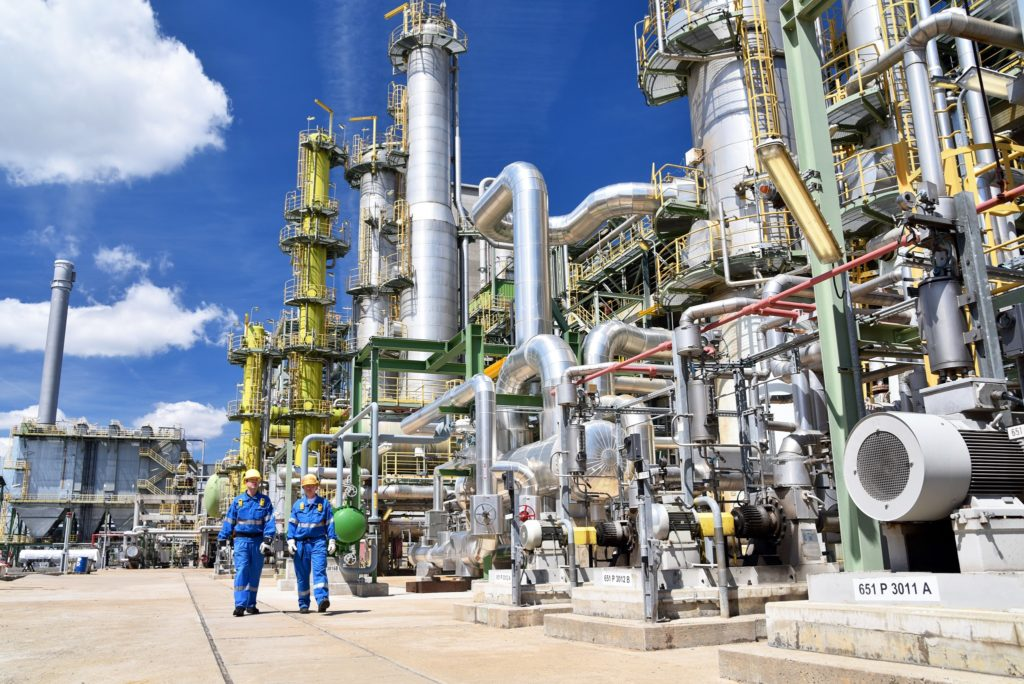 chemical industry plant - workers in work clothes in a refinery with pipes and machinery, cold spray technology can assist this industry