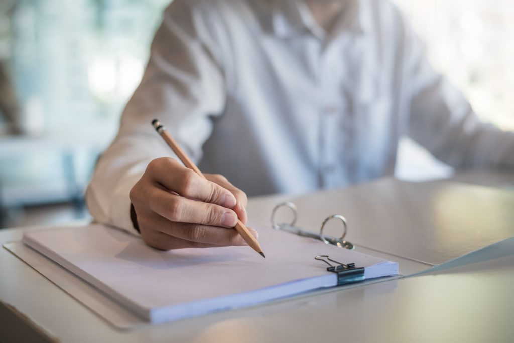 Close up of a woman holding a pencil taking notes at the office., researchers kept track of interesting findings for cold spray technology