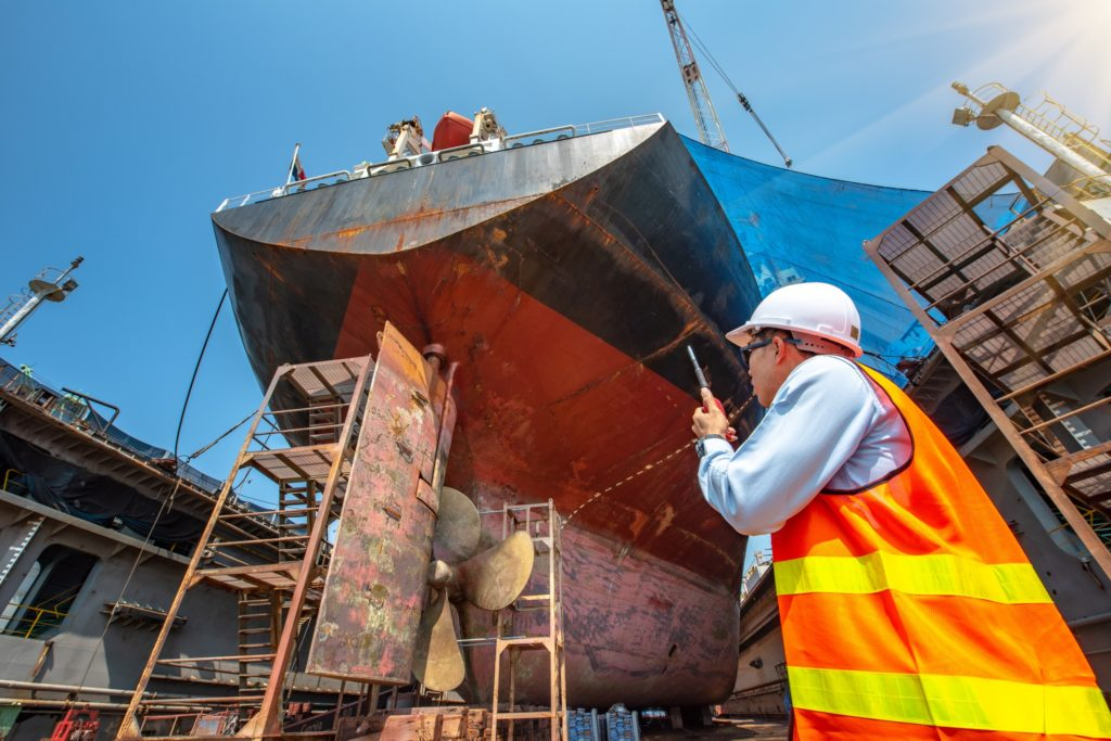 Port Master, surveyor inspecting the bulkhead of commercial cargo ship in floating dry dock, recondition of overhaul repairing and painting, sand blasting, or cold spray repair in dry dock yard