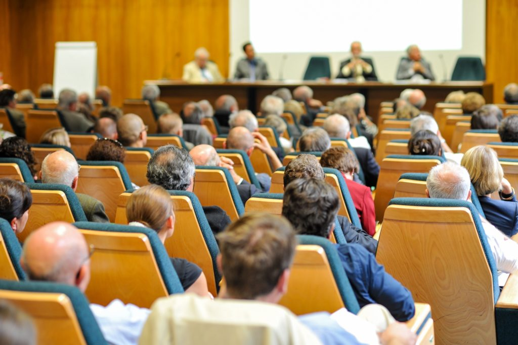 a group of scientists in a symposium, similar to meetings where researchers explained cold spray technology