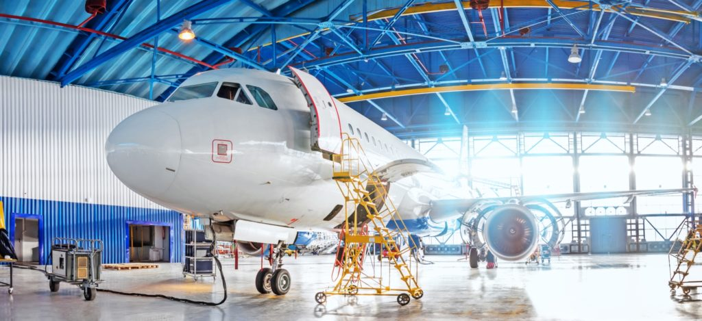 An airplane getting ready for repair in a hangar.